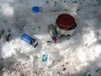A light kitchen and water maker for three. Note that the snow is just melted and then filtered, not boiled, saving coleman costs. MSR Dragonfly stove, pot and heat exchanger, Nalgene and Platypus bags, and Katadyn Mini filter.