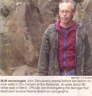BLM archiologist stands before damaged pictographs